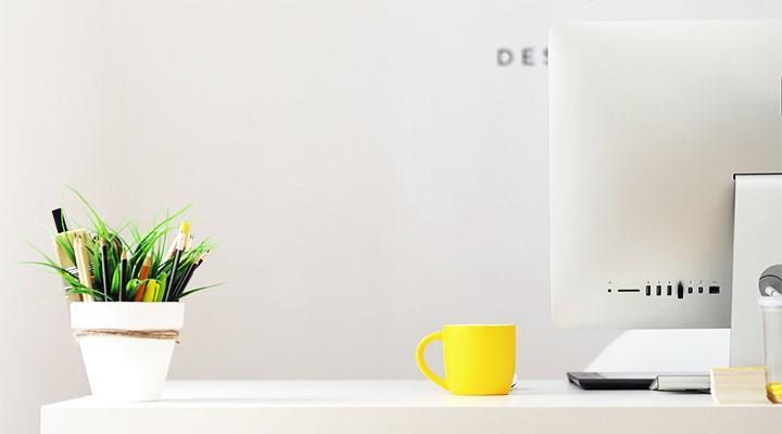 Escritorio con taza, ordenador y maceta