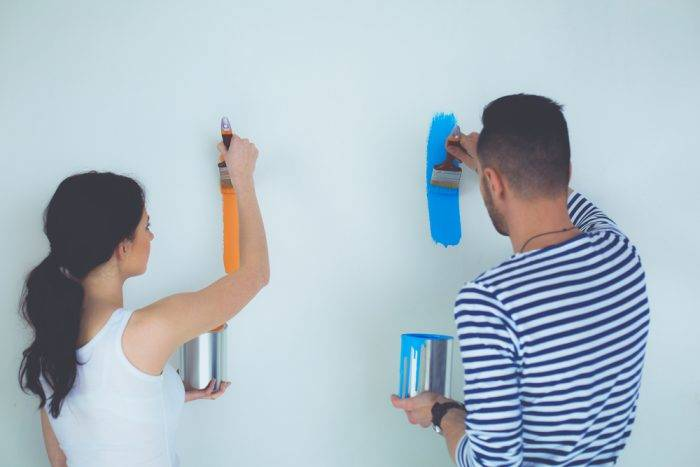 dos jóvenes pintando una pared