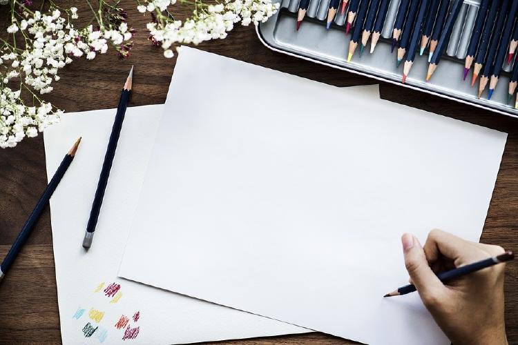 Una persona escribiendo en un folio en blanco