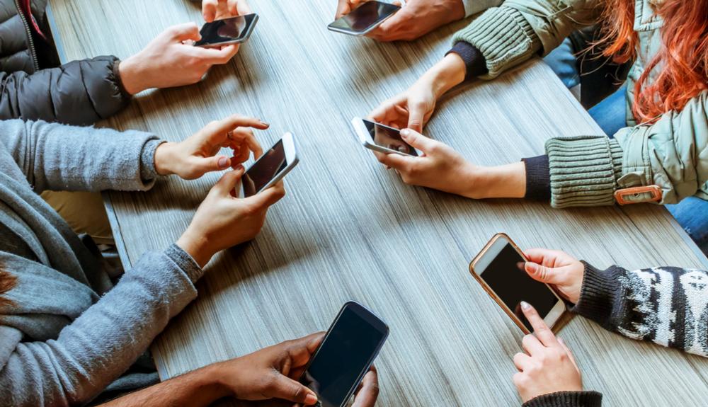 varias personas con móviles en la mano