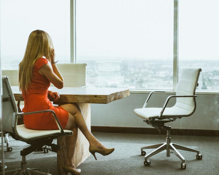Una mujer sentada en la silla dentro de su despacho en la oficina