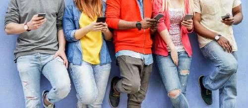 cuatro jóvenes con móviles en la mano