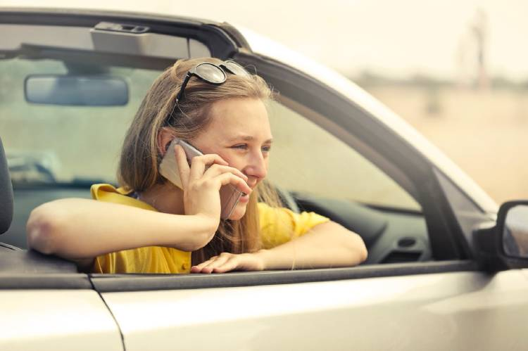 Mujer hablando por el móvil en el coche
