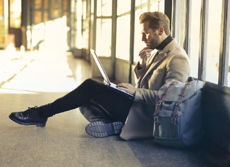 Hombre sentado en el suelo mirando unos papeles