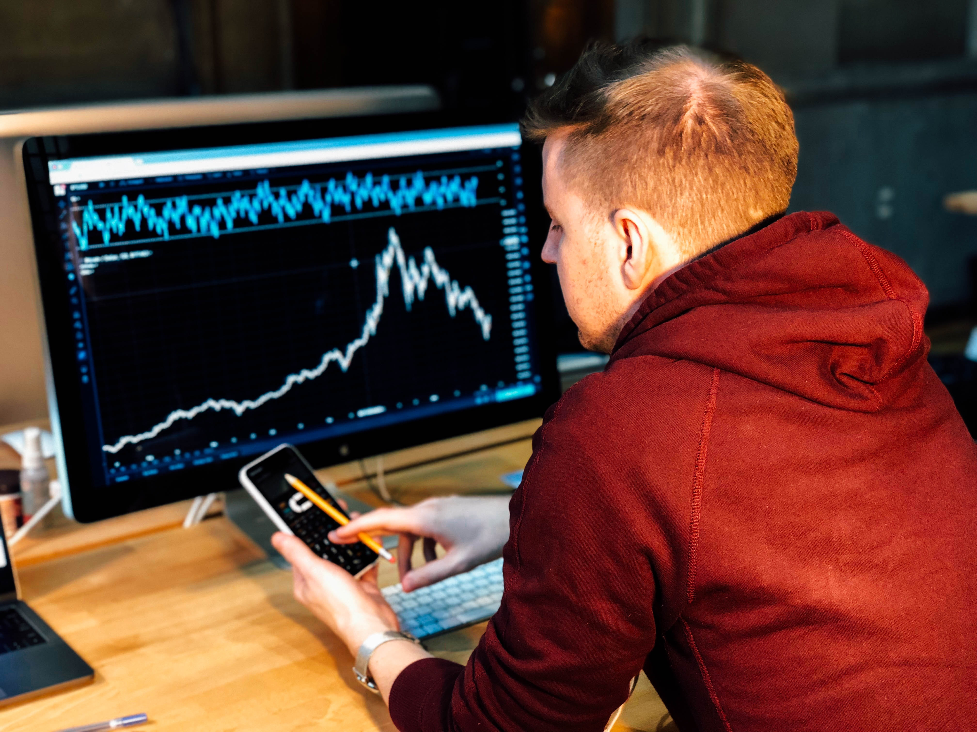 Hombre con el móvil mirando una gráfica
