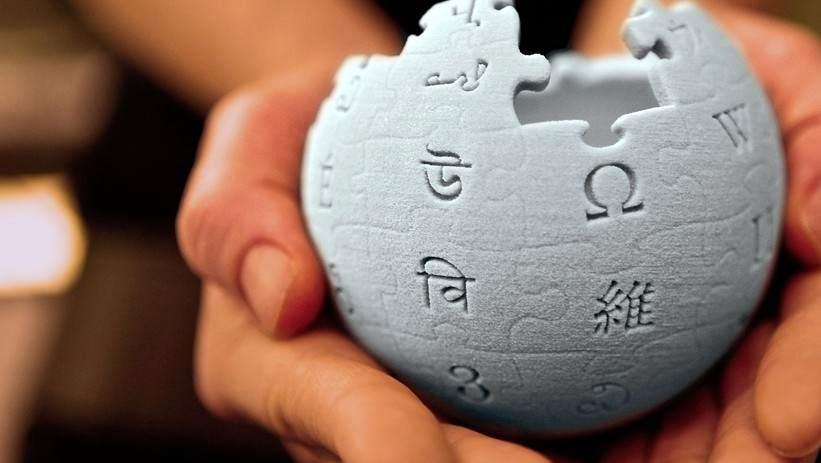 mano sujetando el logo de la wikipedia