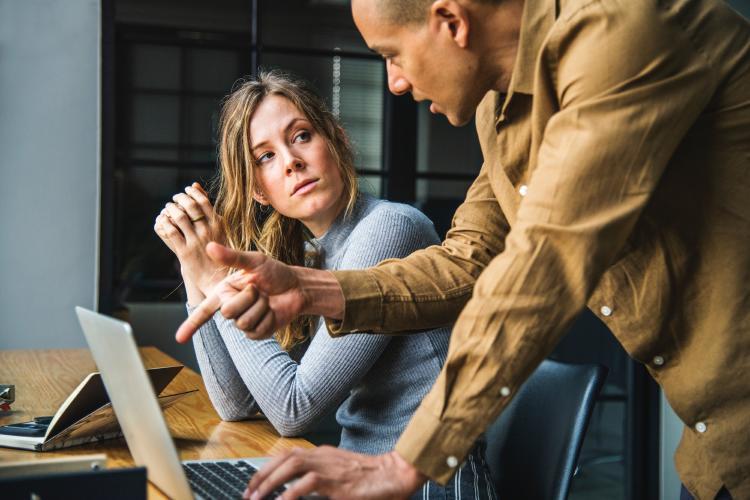 Hombre señalándole la pantalla del ordenador a una mujer