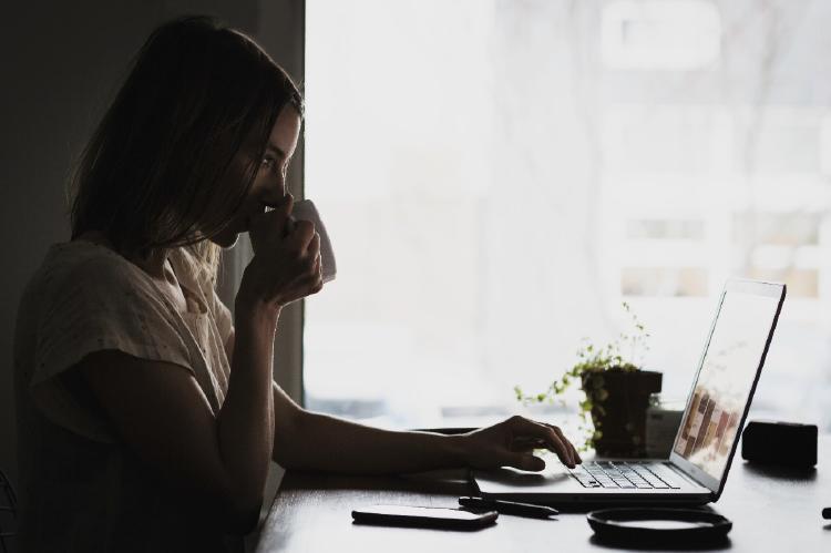 Chica bebiendo café y mirando el ordenador.